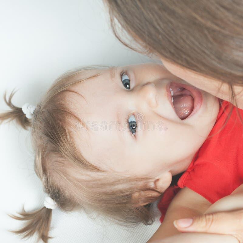 说谎在白色床上的愉快的母亲附近的滑稽的女婴 库存图片