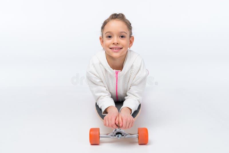 说谎在白色的滑板的微笑的女孩 免版税库存照片
