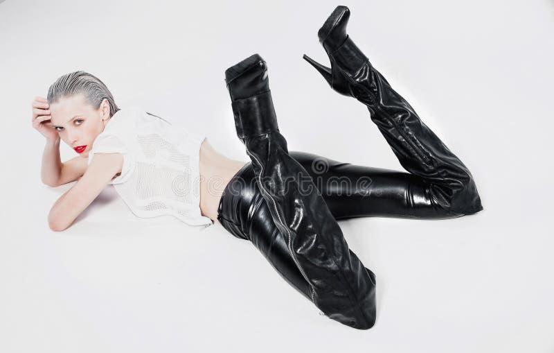 说谎在白色背景的黑绑腿的女孩 免版税库存图片