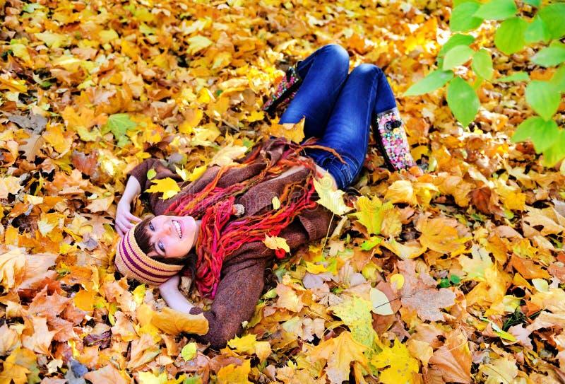 说谎在秋叶的妇女画象在公园 库存图片