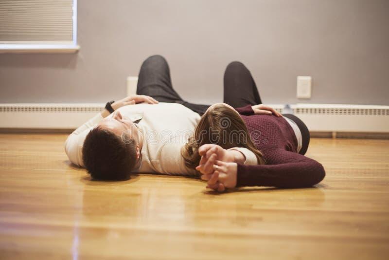 说谎在空的地板上的夫妇 免版税库存照片