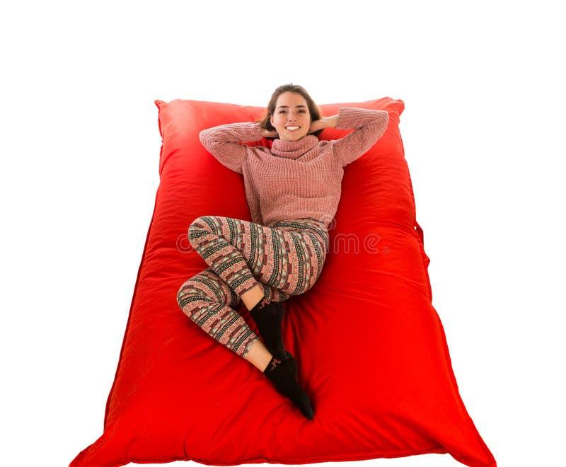 说谎在红场的美丽的妇女塑造了被隔绝的装豆子小布袋沙发 免版税库存照片