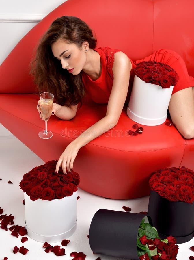 说谎在红色嘴唇沙发长沙发的美丽的豪华时髦的女人 库存照片