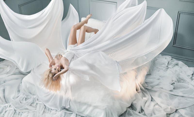 说谎在纯净的白色板料的可爱的白肤金发的夫人 免版税库存图片