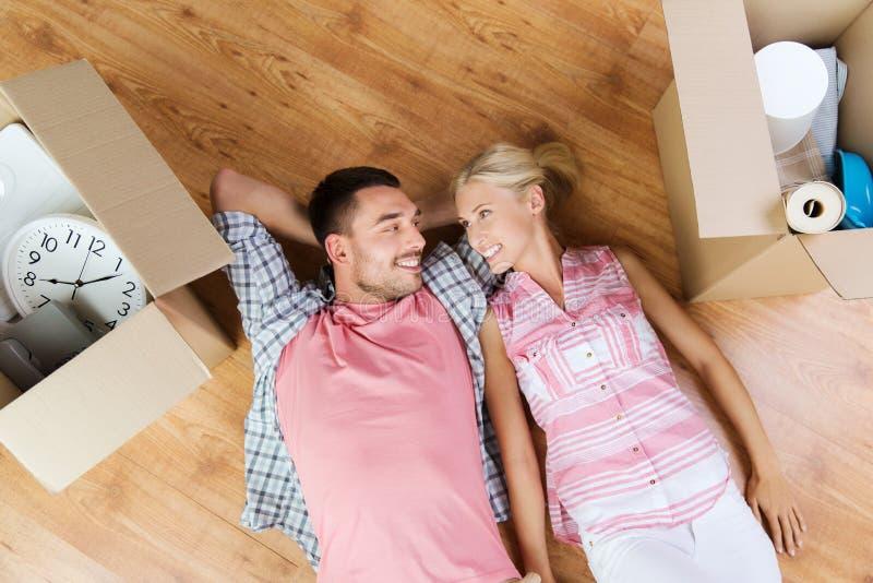 说谎在纸板箱中的地板上的愉快的夫妇 库存照片