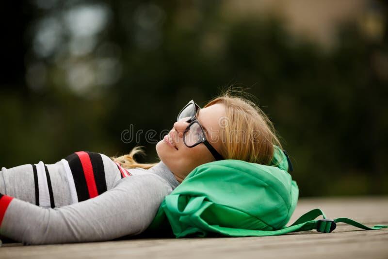 说谎在背包的自然的梦想的女孩 库存照片