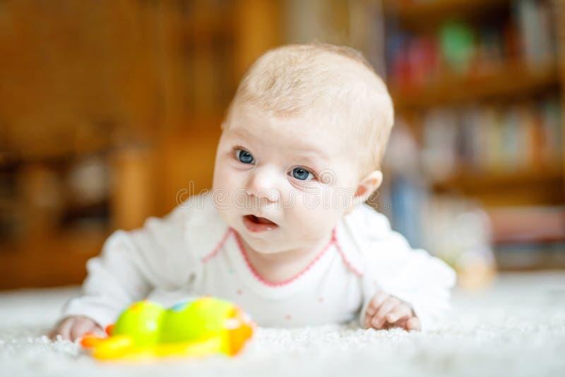 说谎在腹部的可爱的新出生的女婴在白色晴朗的卧室或托儿所 免版税库存照片