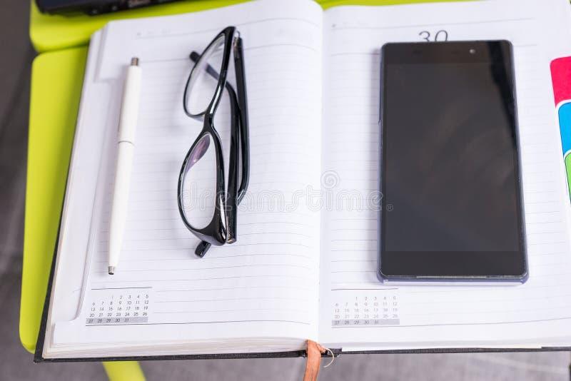 说谎在膝上型计算机桌上的手机附近的时髦的玻璃 库存照片