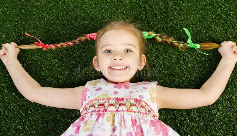 说谎在草的Smililing愉快的小女孩 免版税库存照片
