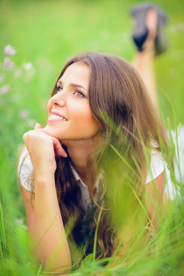 说谎在草和花中的愉快的微笑的美丽的女孩 库存照片