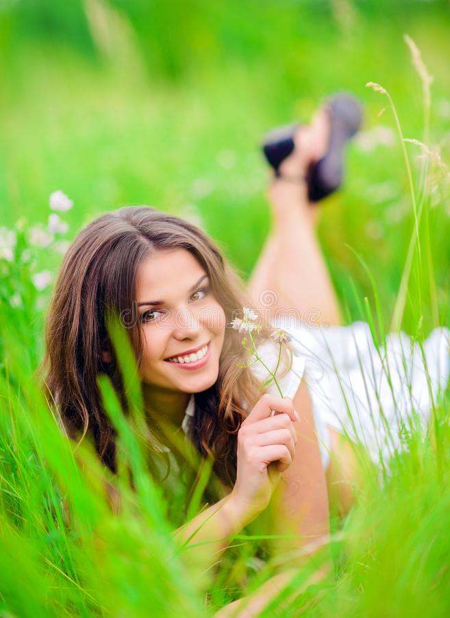 说谎在草和花中的愉快的微笑的美丽的女孩 库存图片