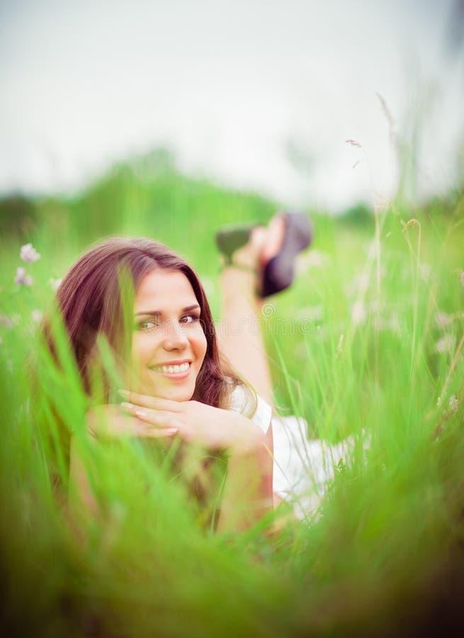说谎在草和花中的愉快的微笑的美丽的少妇 免版税库存图片
