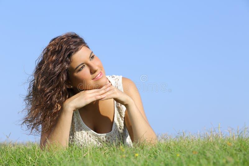 说谎在草的一名美丽的妇女的画象 免版税库存图片