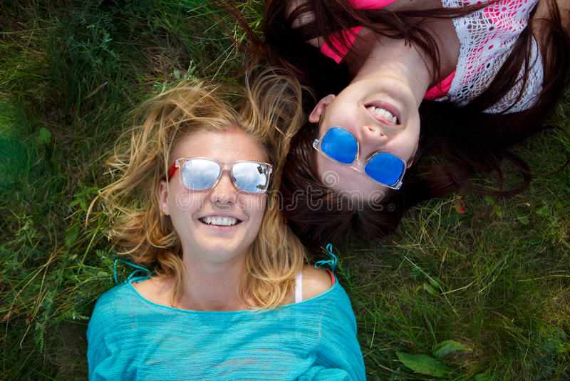 说谎在草的太阳镜的微笑的少妇 库存图片