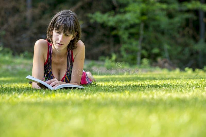 说谎在草的妇女,当读书时 库存图片