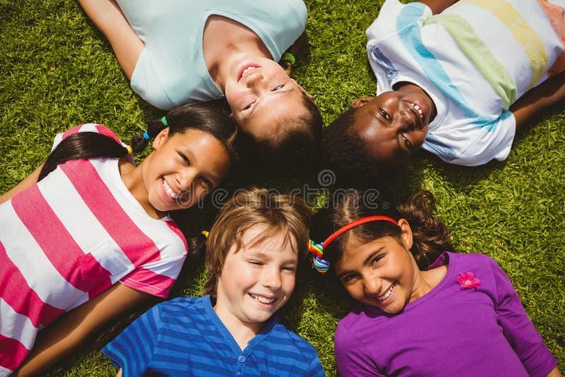说谎在草的孩子画象在公园 免版税库存照片