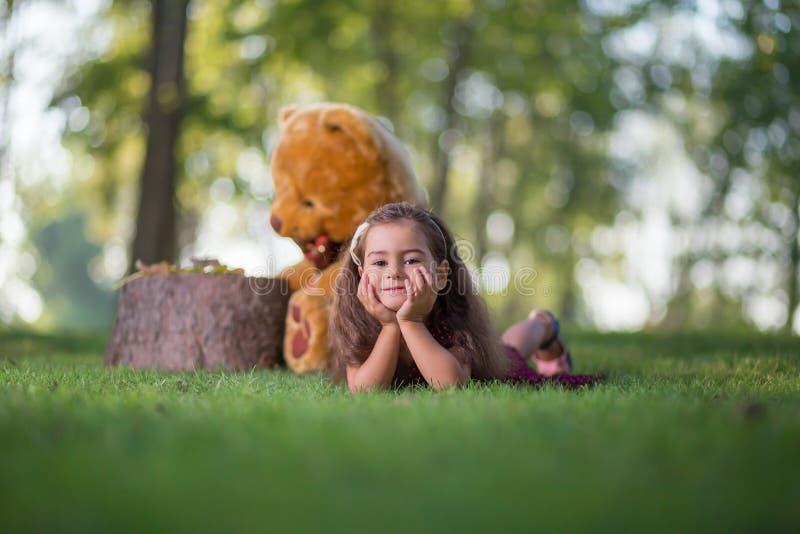 说谎在草的小女孩在公园 免版税图库摄影