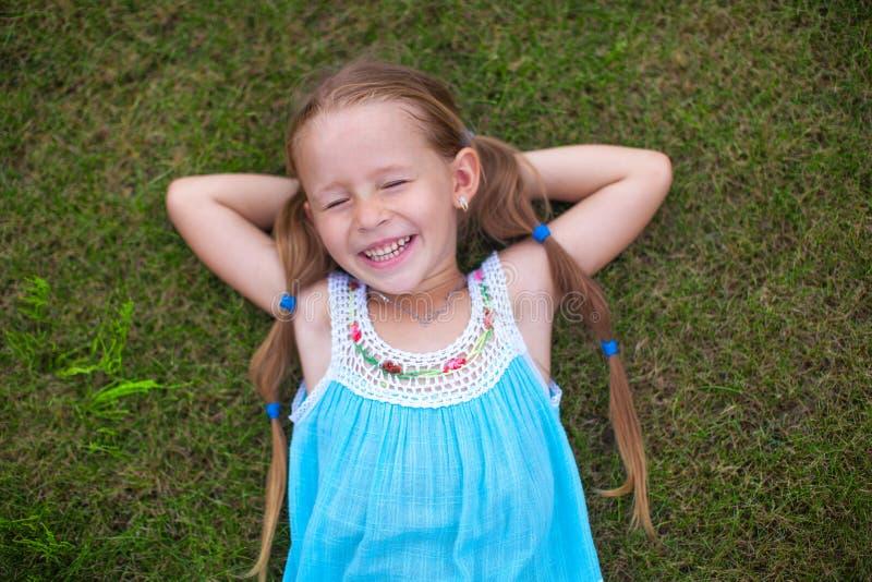 说谎在草的小女孩在房子附近和 免版税库存照片