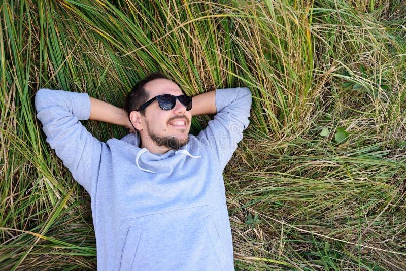 说谎在草的微笑的人 免版税库存图片