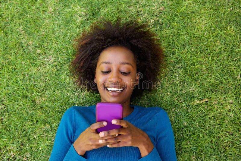 说谎在草的微笑的非洲妇女看手机 免版税图库摄影
