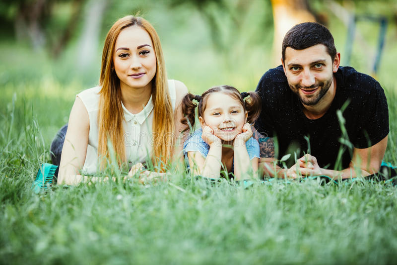 说谎在草的愉快的三口之家 愉快的家庭关系和无忧无虑的业余时间的概念 免版税库存照片
