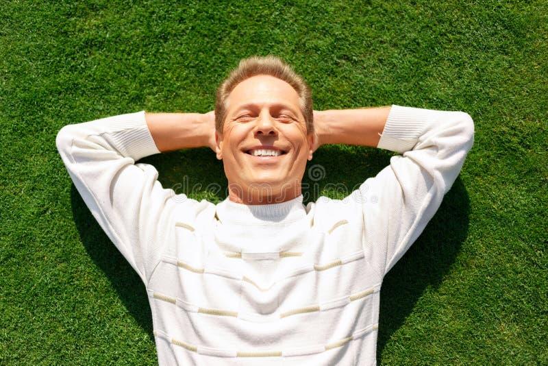 说谎在草的愉快的人 免版税库存照片