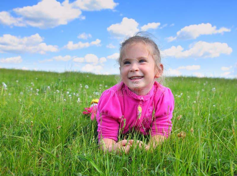 说谎在草的愉快的小女孩 库存图片