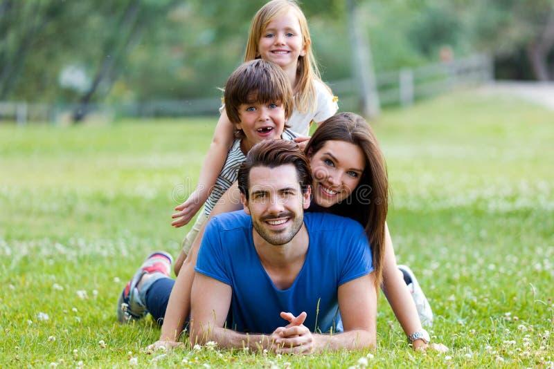 说谎在草的愉快的年轻家庭 图库摄影
