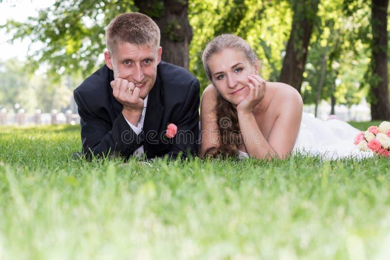 说谎在草的新娘和新郎画象  库存照片