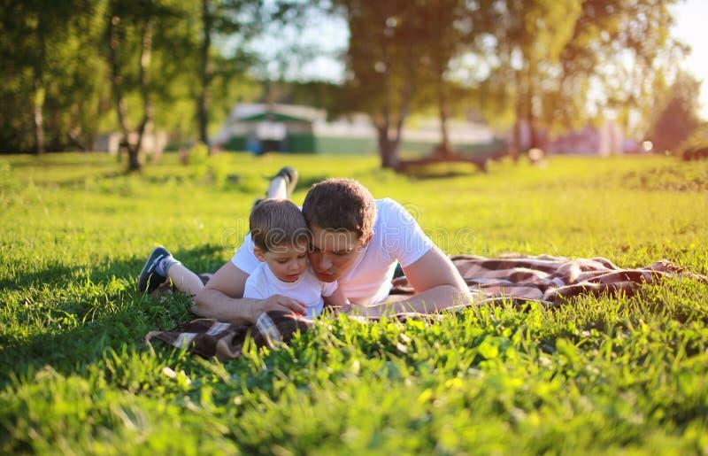 说谎在草的父亲和儿子在周末,家庭,假期 免版税库存图片