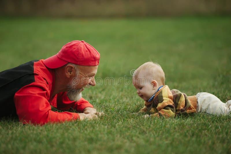 说谎在草的祖父和孙子 图库摄影