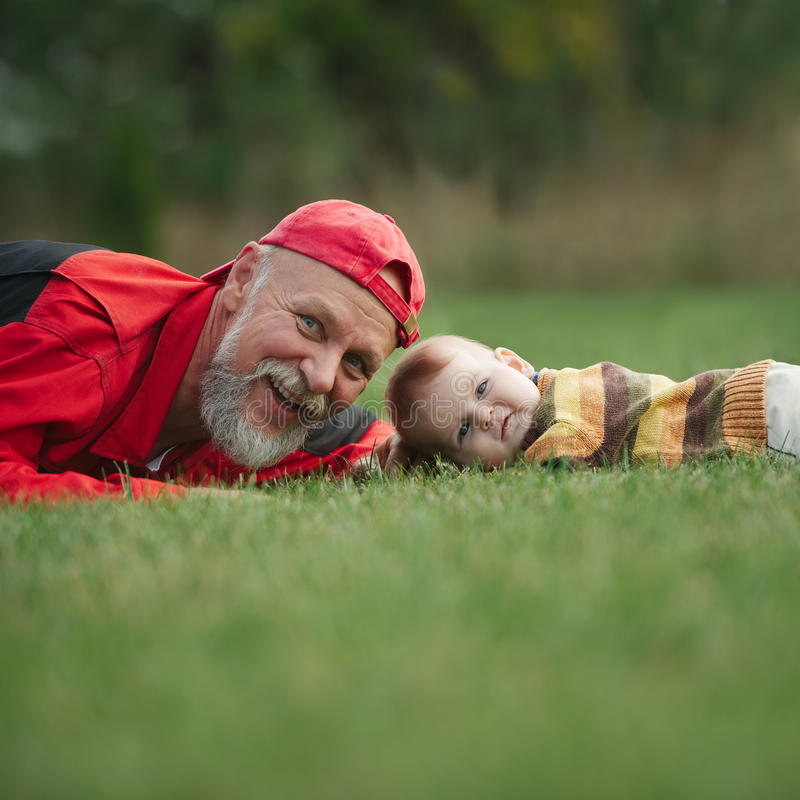 说谎在草的祖父和孙子 库存照片