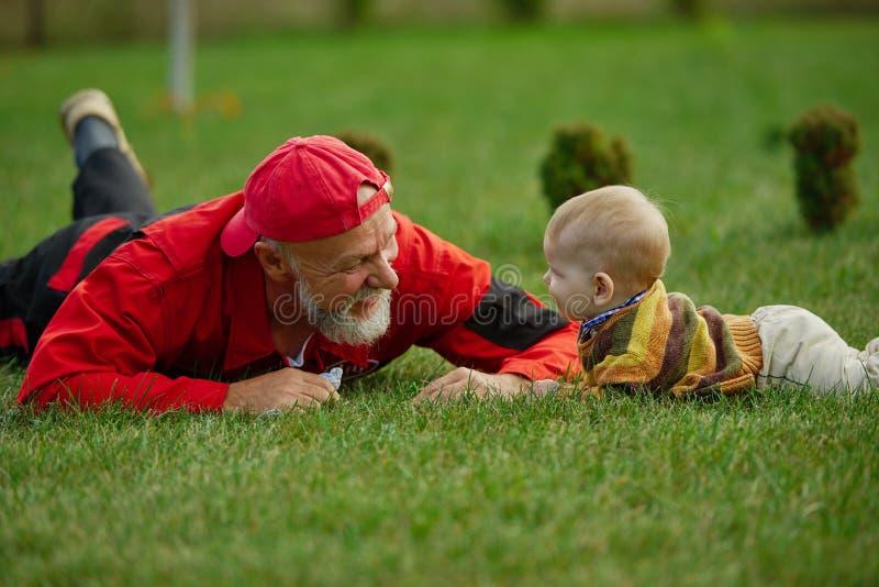 说谎在草的祖父和孙子 免版税库存照片