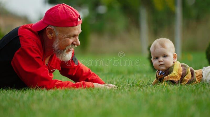 说谎在草的祖父和孙子 免版税库存图片