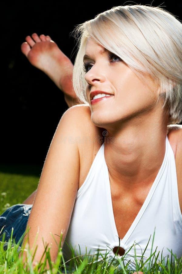 说谎在草的美丽的被晒黑的少妇 免版税库存图片