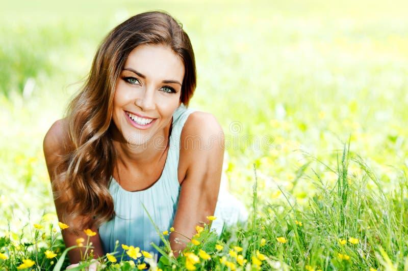 说谎在草的蓝色礼服的妇女 免版税库存照片