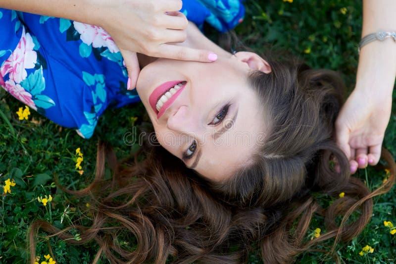 说谎在草的蓝色礼服的轻松的美丽的少妇 免版税图库摄影