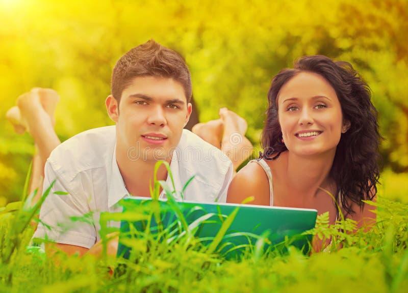 说谎在草的年轻夫妇微笑和看照相机 免版税图库摄影