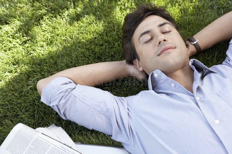 说谎在草的轻松的商人在公园 免版税库存图片