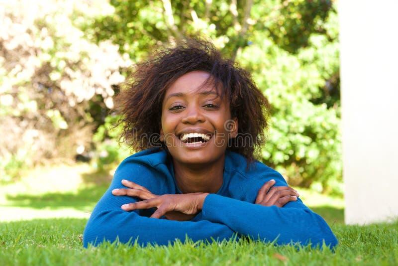 说谎在草笑的可爱的年轻黑人妇女 免版税库存图片