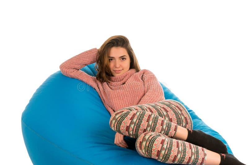 说谎在蓝色装豆子小布袋沙发的美丽的妇女隔绝在白色bac 库存照片