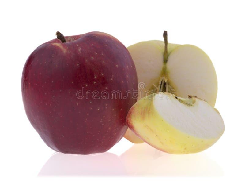说谎在被切的ââapples旁边的鲜美成熟苹果,被隔绝  免版税库存照片