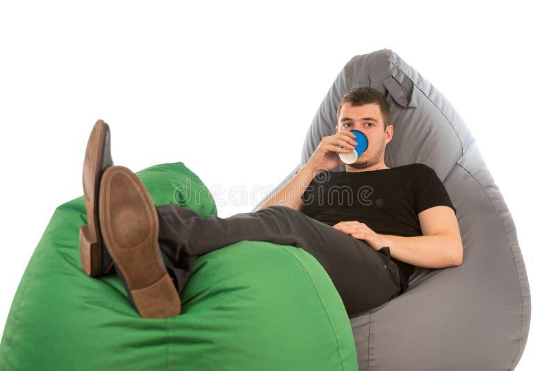 说谎在装豆子小布袋椅子和饮用的咖啡的年轻人 库存图片