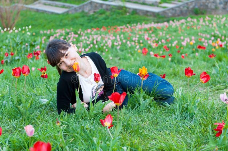 说谎在郁金香中的微笑的少妇在春天 免版税库存照片