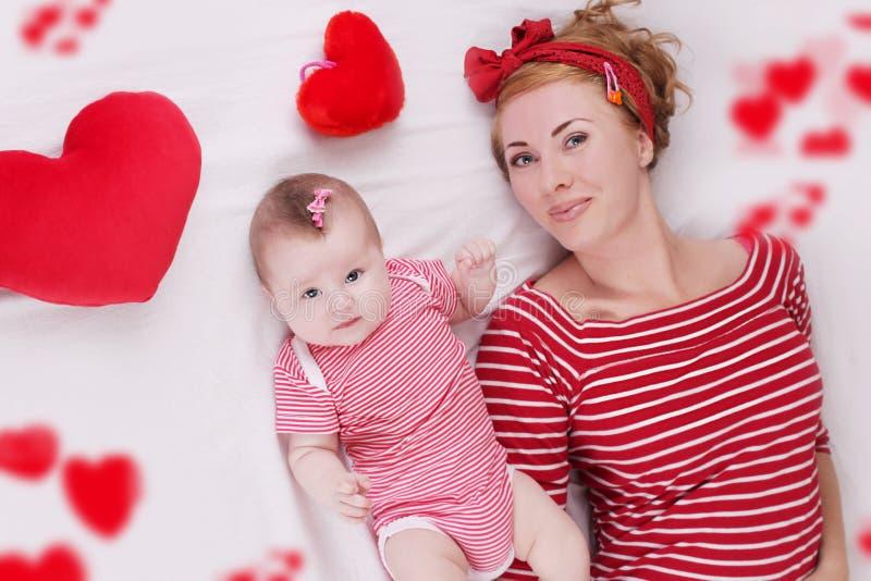 说谎在长毛绒心脏中的女婴和母亲 库存图片