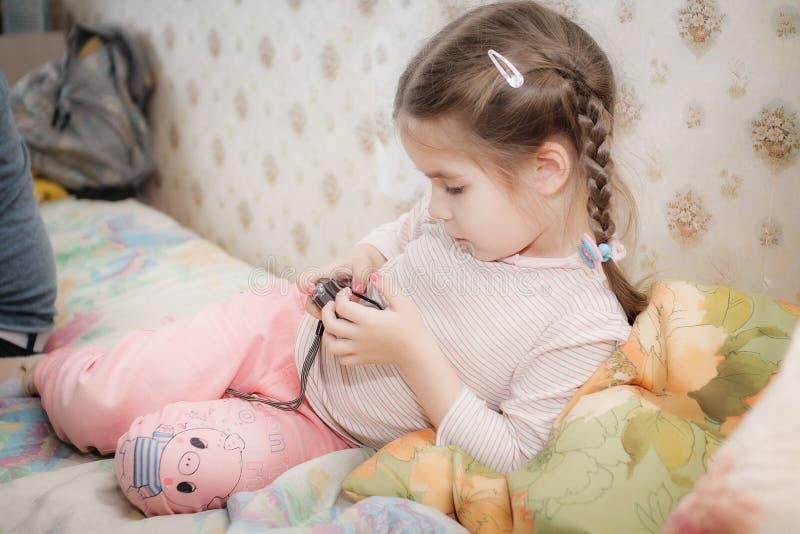 说谎在长沙发和看在照相机的小女孩图片 库存照片