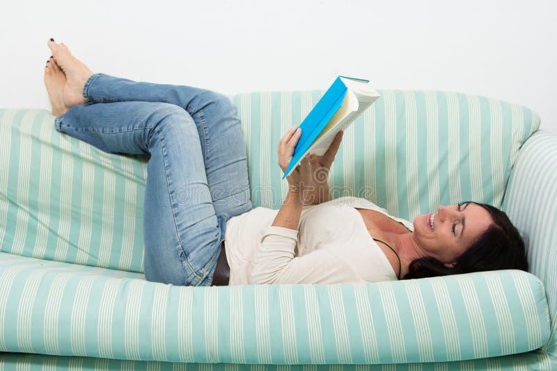 说谎在长沙发和读书的深色头发的妇女 库存照片