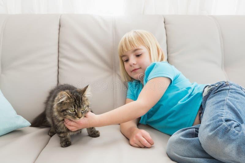 说谎在长沙发的小女孩抚摸她的猫 库存图片