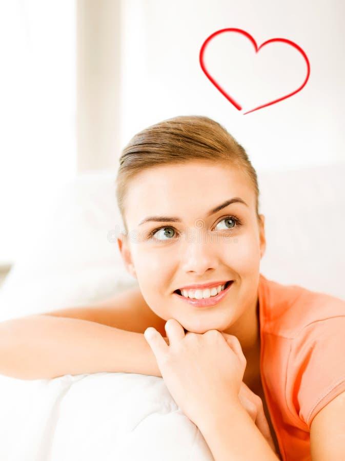 说谎在长沙发的微笑的妇女 免版税图库摄影