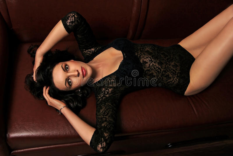说谎在长沙发的性感的女孩 免版税库存图片